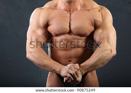 Strong torso and hand muscles of undressed tanned wet bodybuilder - stock photo