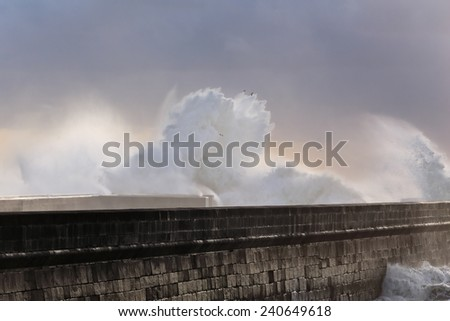 Strong waves crashing against pier with interesting end-of-day light filtered through the clouds and moisture. Porto, Portugal, in January. - stock photo
