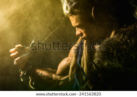 Strong werewolf, demon among the trees in the fog. The image of a formidable enemy with long nails - stock photo