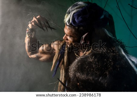 Strong werewolf, demon among the trees. The image of a formidable enemy with long nails - stock photo