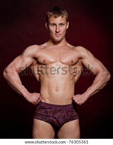 Strong wet sexy nude young bodybuilder posing - stock photo