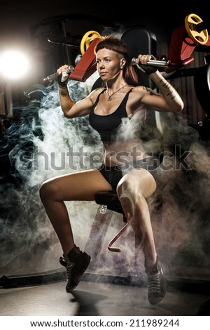 Strong woman at the gym doing exercises on a machine  - stock photo