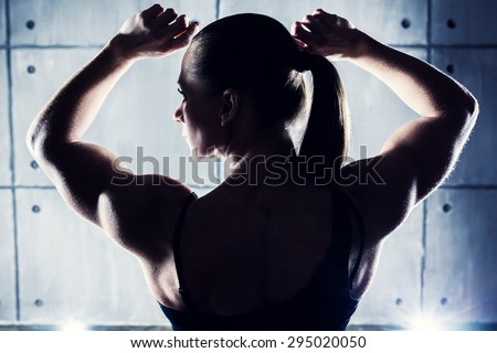 Strong woman bodybuilder back view. Contrast silhouette on wall background. - stock photo