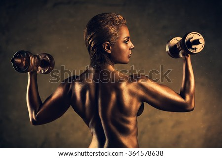 Strong woman bodybuilder standing nude on wall background. Ancient bronze statue concept. - stock photo