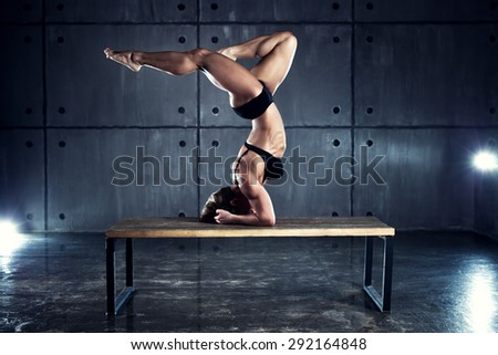 Strong woman bodybuilder standing upside down on table on wall background. - stock photo
