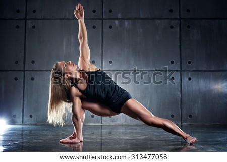 Strong woman bodybuilder stretching on wall background. - stock photo