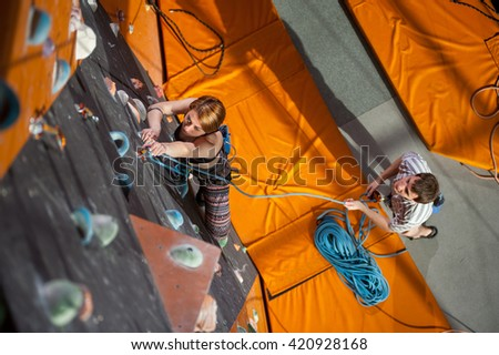 Strong woman climber with carbines and rope on an indoor rock-climbing wall is climbing up. Man standing on the ground insuring the climber