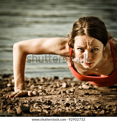 Strong woman doing push up at the beach - stock photo