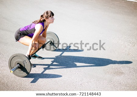 Strong woman exercising with barbell in gym. Cute girl preparing for weightlifting workout. Sports, fitness concept.