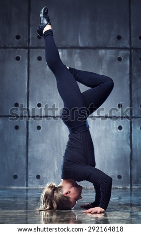 Strong woman gymnast in black clothing standing upside down on wall background. - stock photo