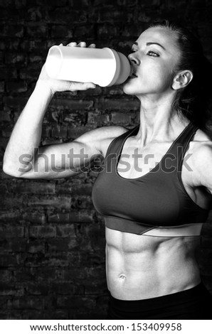 strong woman is drinking sports nutrition - stock photo
