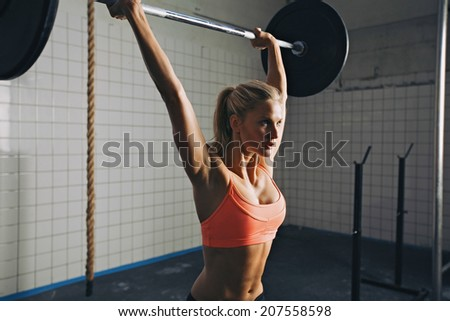 Strong woman lifting barbell as a part of crossfit exercise routine. Fit young woman lifting heavy weights at gym. - stock photo