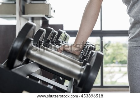 Strong woman's hand takes a heavy dumbbell in gym