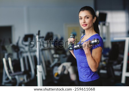 Strong woman weightlifting at the gym. Woman working out with dumbbells at a gym. Dumbbell bicep curl by a fitness girl. In good condition. - stock photo