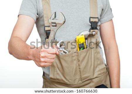Strong worker holding a spanner on white isolated background - stock photo