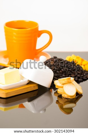 Strong yellow coffe cup on shiny surface sourrounded by cheese, small toasts and coffee beans. - stock photo