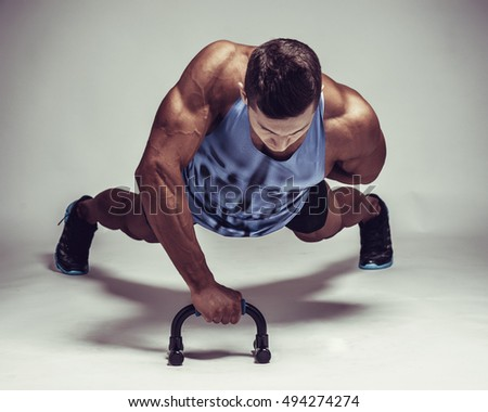Strong young athlete doing push-ups on one hand. Sports concept.
