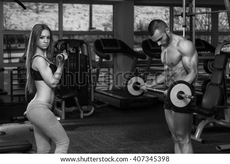 Strong Young Couple Doing Exercise For Biceps With Dumbbells And Barbell In The Gym - stock photo