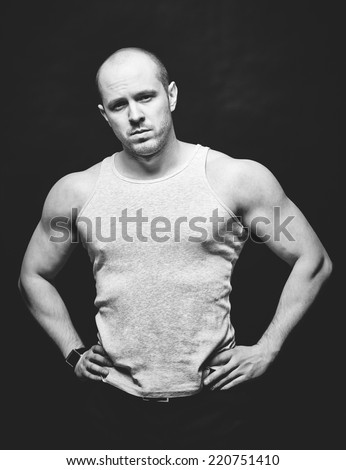 Strong young man in vest looking at camera - stock photo