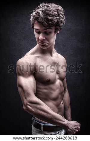 Strong young man looked down dissatisfied to his arm muscles - stock photo