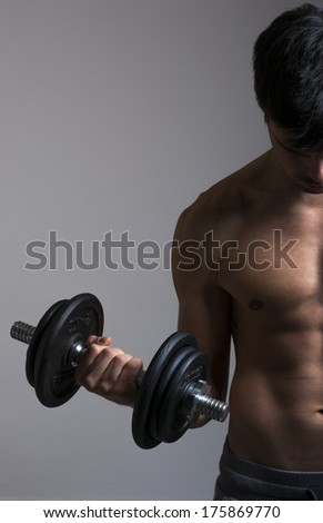 Strong young man with dumbbells on gray background