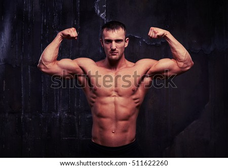 Strong young man with perfect abs, shoulders, biceps, triceps and chest is posing bare-chested in dark studio