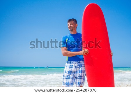 Strong young surf man at the beach with a surfboard.