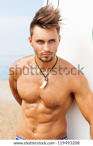 Strong young surf man portrait at the beach with a surfboard - stock photo