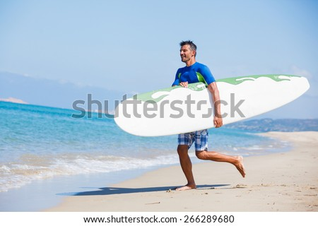 Strong young surf man runing at the beach with a surfboard. - stock photo