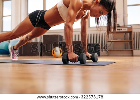 Strong young woman doing push ups exercise with dumbbells on yoga mat. Fitness model doing intense training in the gym.