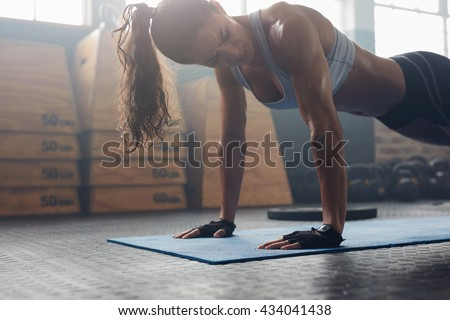 Strong young woman doing push-ups in gym. Fit female exercising in health club. - stock photo