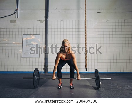 Strong young woman lifting heavy weights at gym. Fitness female doing crossfit workout. - stock photo