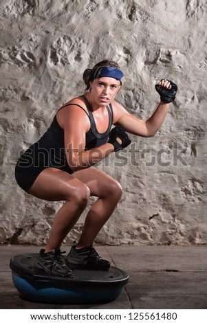 Strong young woman on balance ball bending with arms up - stock photo
