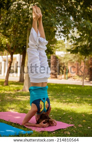 Strong young woman practicing the headstand yoga pose at a park - stock photo