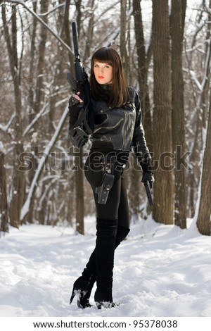 Strong young woman with a rifle in forest - stock photo