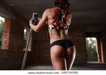 Strong young woman with beautiful athletic body doing exercises with barbell. Fitness, bodybuilding. Health care. Lifestyle, diet and fitness - stock photo