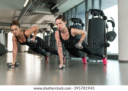 Strong Young Women Doing Exercise With Dumbbells In The Gym