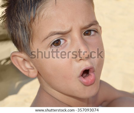 Stroppy child at the beach says something