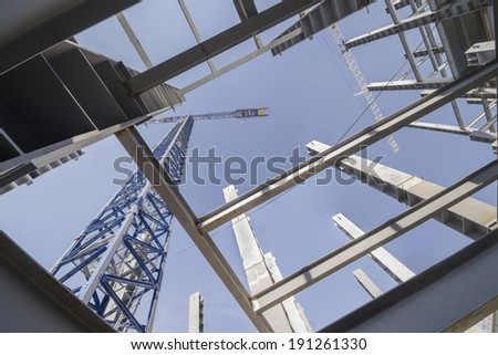 Structural design and jib crane Low-angle shot of a several metal columns and girders of a construction site  - stock photo