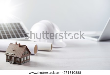 Structural engineer and architect desktop with safety helmet, solar panel and model house - stock photo