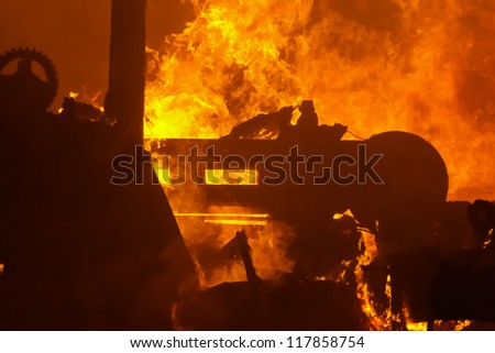 Structure fire silhouetted shapes, heavy flame and smoke - stock photo