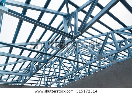 Structure of steel roof frame for building construction on sky background.
