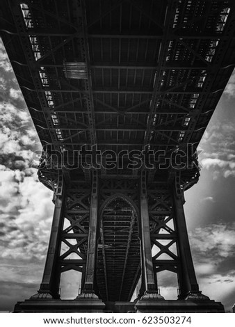 Structure under Manhattan bridge with cloudy sky in black and white style
