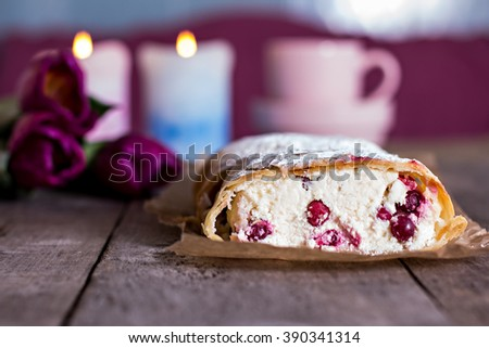 Strudel or pie, tulips and envelope on an old wooden table - stock photo