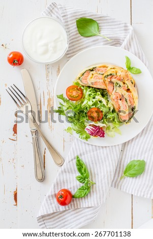 Strudel pie with salmon and spinach, served on white plate with salad, cherry tomatoes, sour cream, white wood background, top view