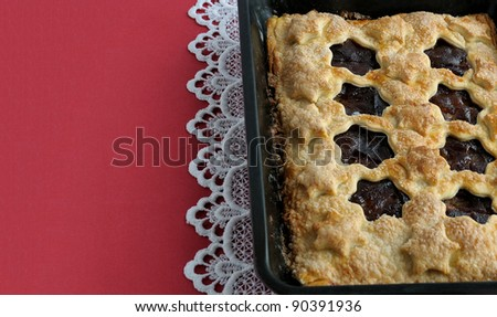 Strudel Stuffed With Apples And Jam On A Red Tablecloth With White Laces