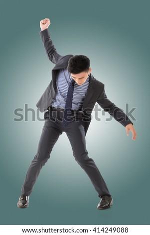 Struggle pose of Asian business man, full length isolated. - stock photo
