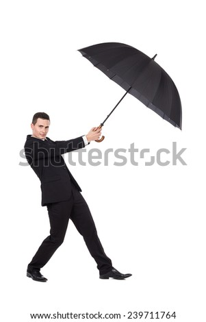 Struggle with the wind. Elegance man holding an open umbrella. Full length studio shot isolated on white. - stock photo