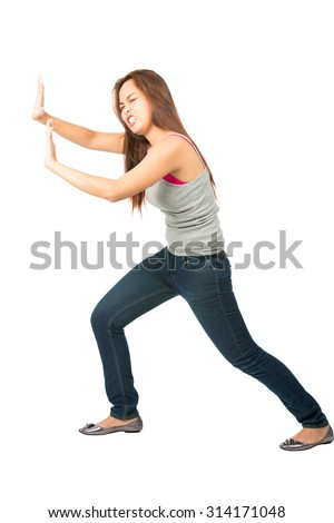Struggling Asian woman in casual clothes, extended arms, defending, protecting, forcing, leaning body weight, pushing and fighting against imaginary (insert) object moving in from side - stock photo