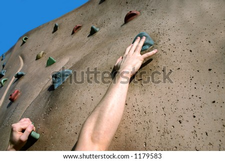 Struggling to reach handhold on climbing wall - stock photo